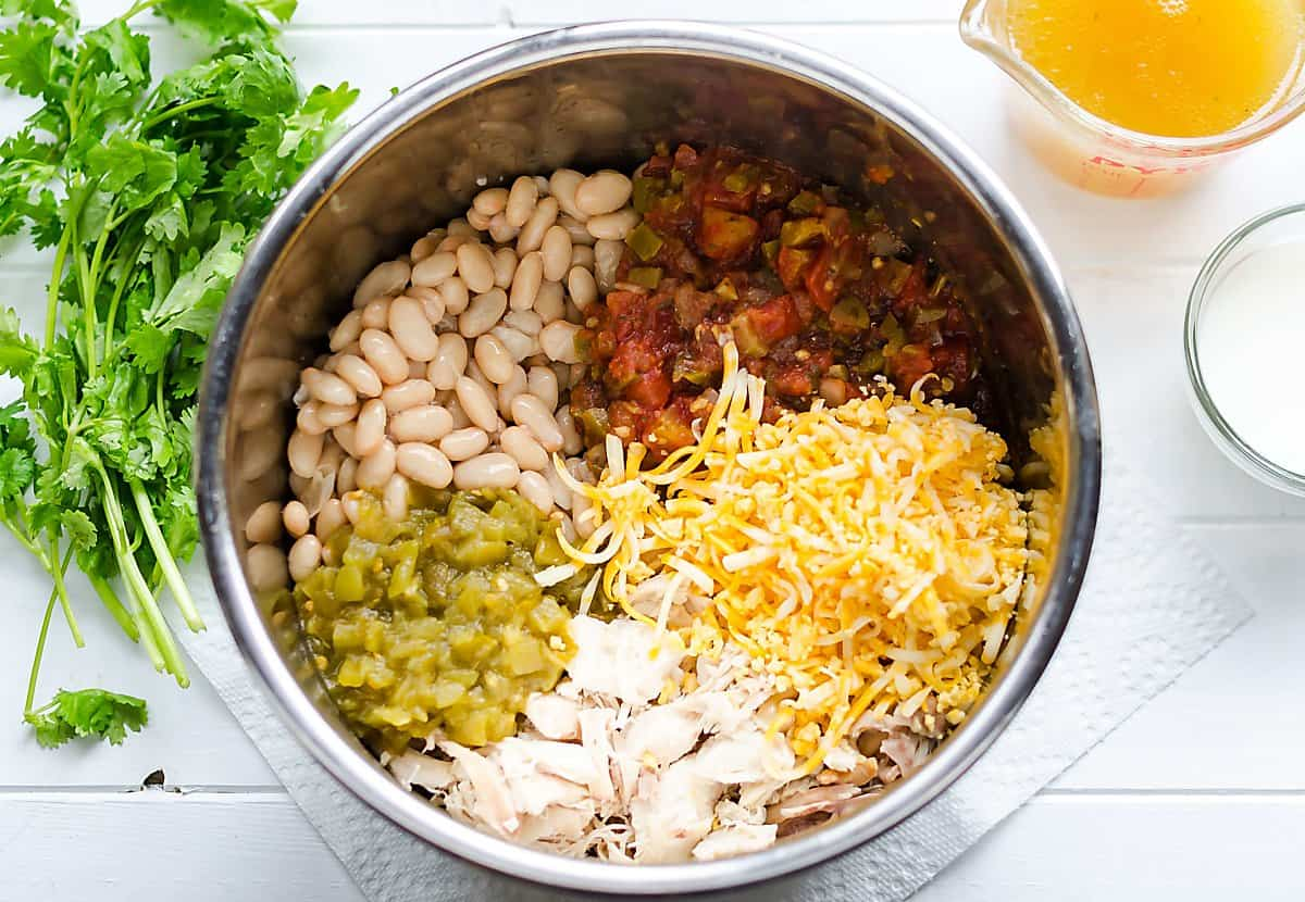 crockpot/instant pot filled with white chicken chili ingredients and segmented-white beans, salsa, green chilies, chicken and cheeese