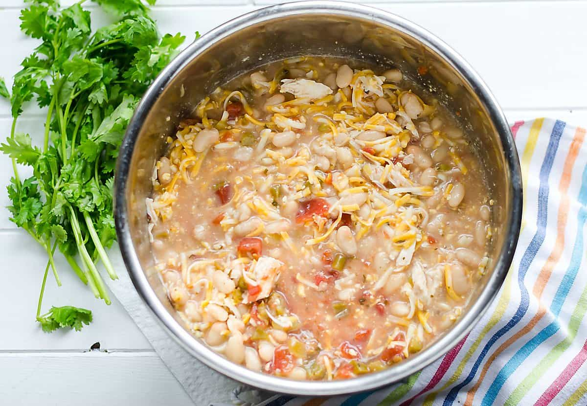 slow cooker/instant pot with white chicken chili ingredients in it before cooked
