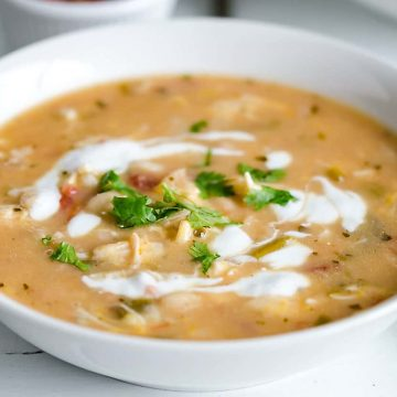 white bowl filled with white chicken chili, garnished with swirls of sour cream and cilantro