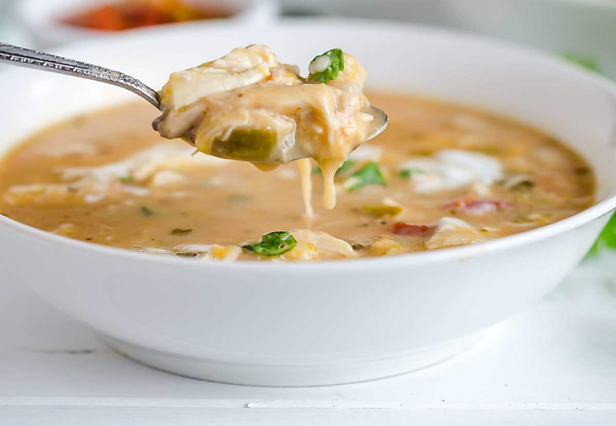 spoonful of white chicken chili hovering over a bowl of chili, cheese dripping off the spoon