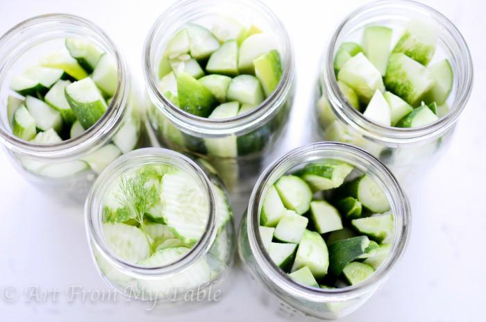 Quart sized Mason jars full of sliced cucumbers and cucumber spears.