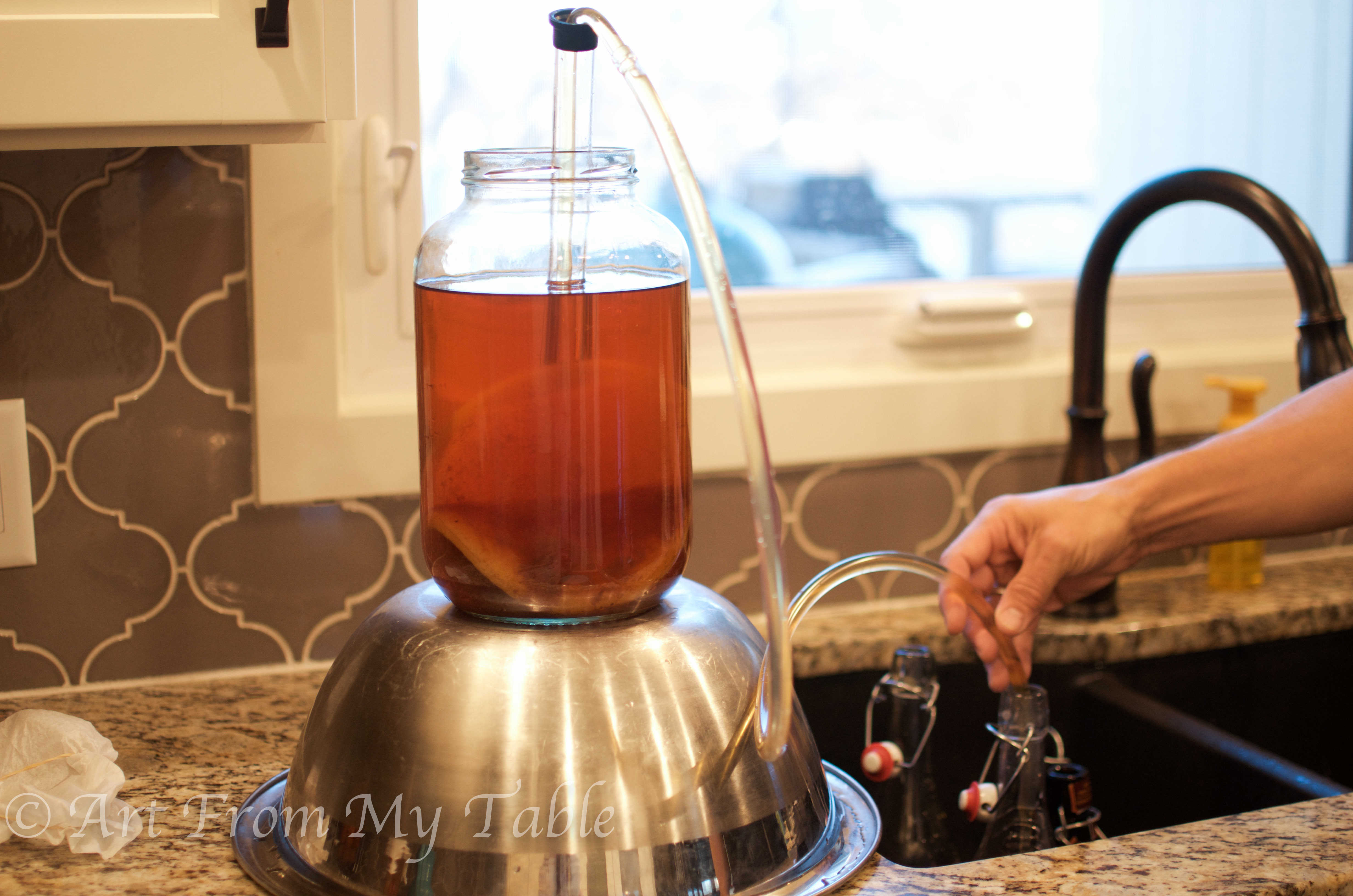 Gallon of tea being siphoned into the bottles with flavorings.