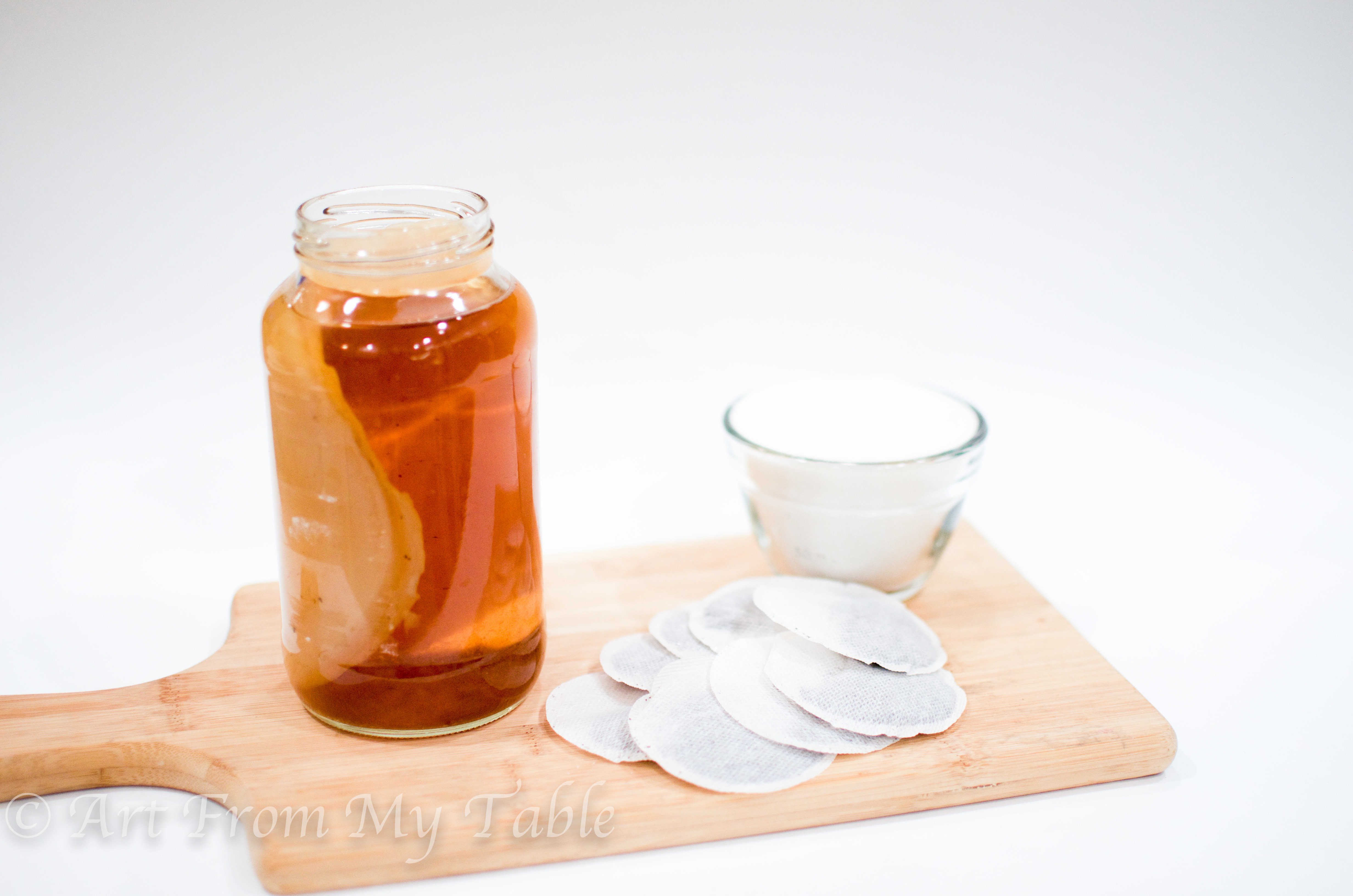 Ingredients for Kombucha: jar of starter tea with a SCOBY in it, black tea bags, and sugar.