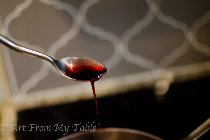 Pomegranate reduction on a spoon.