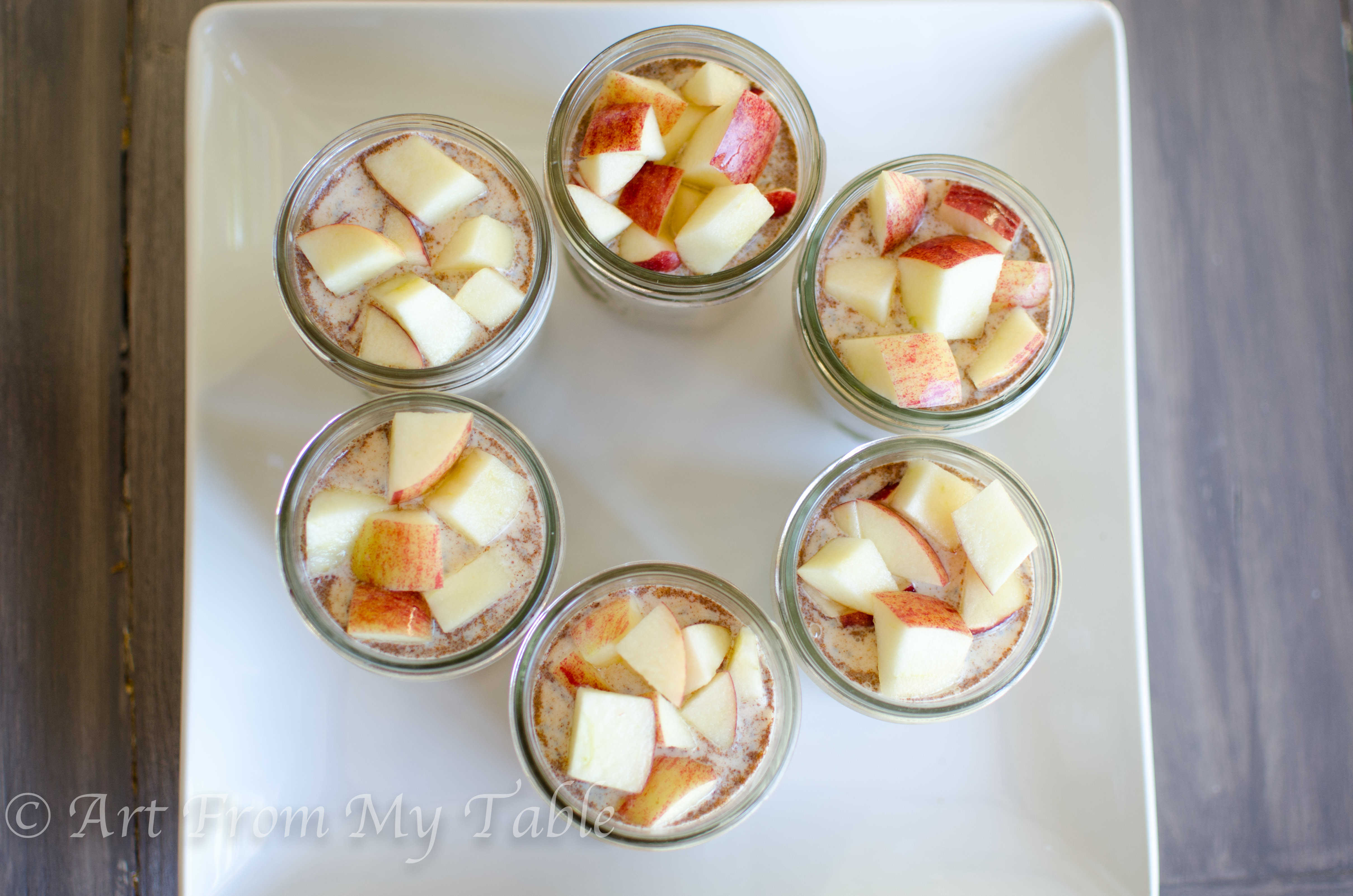Overnight oats with apples and peanut butter in pint sized mason jars on a platter.