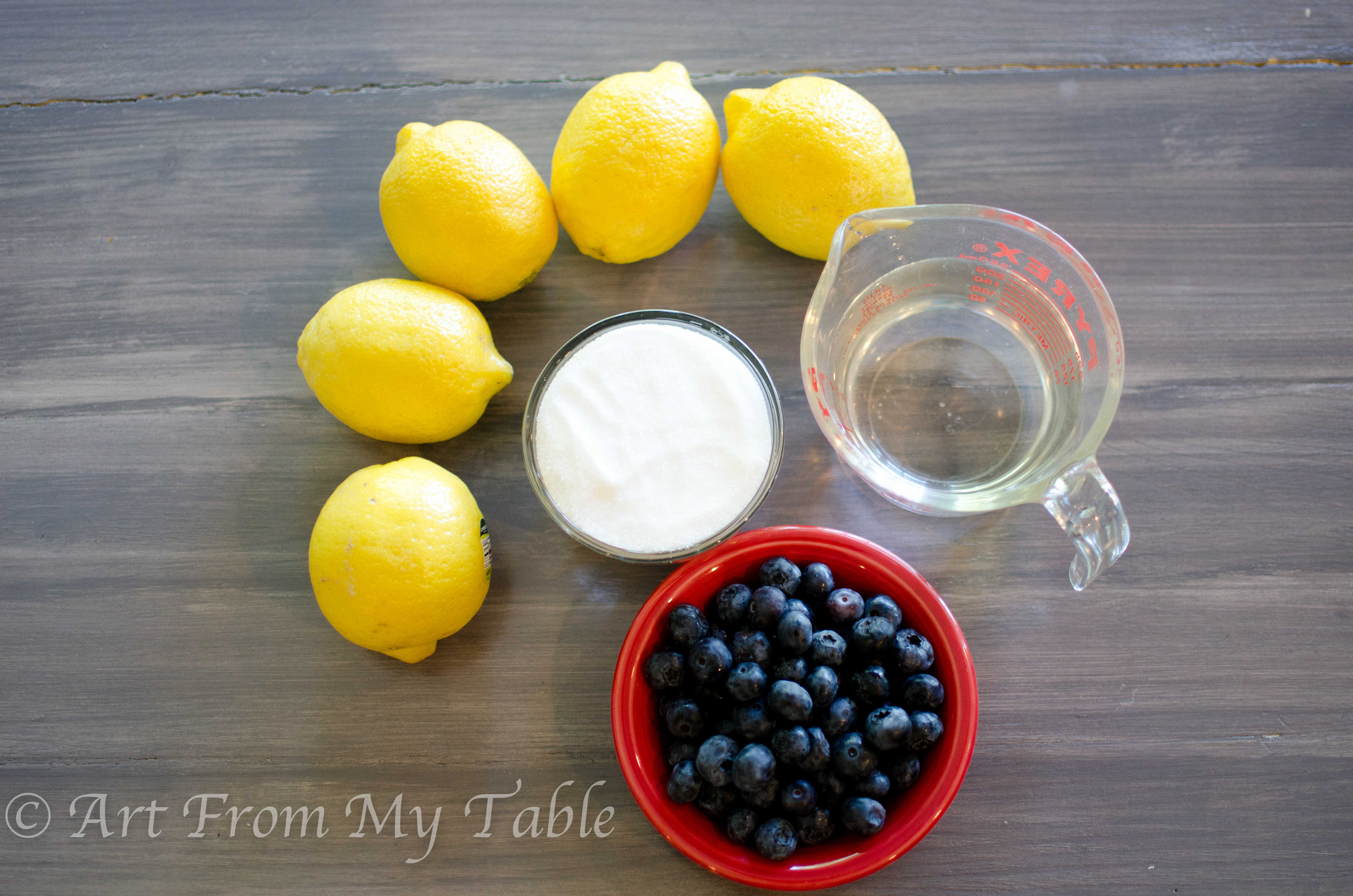 Ingredients for blueberry lemonade: lemons, sugar, water, blueberries.