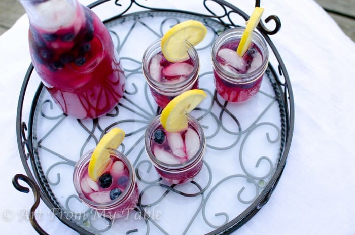 Carafe of blueberry lemonade next to four jars of blueberry lemonade garnished with blueberries and lemon slices.