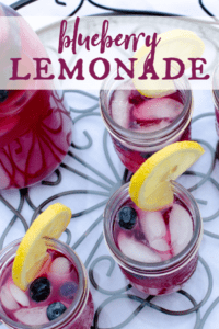one pitcher and 3 mason glasses filled with blueberry lemonade and garnished with lemon slices and fresh blueberries