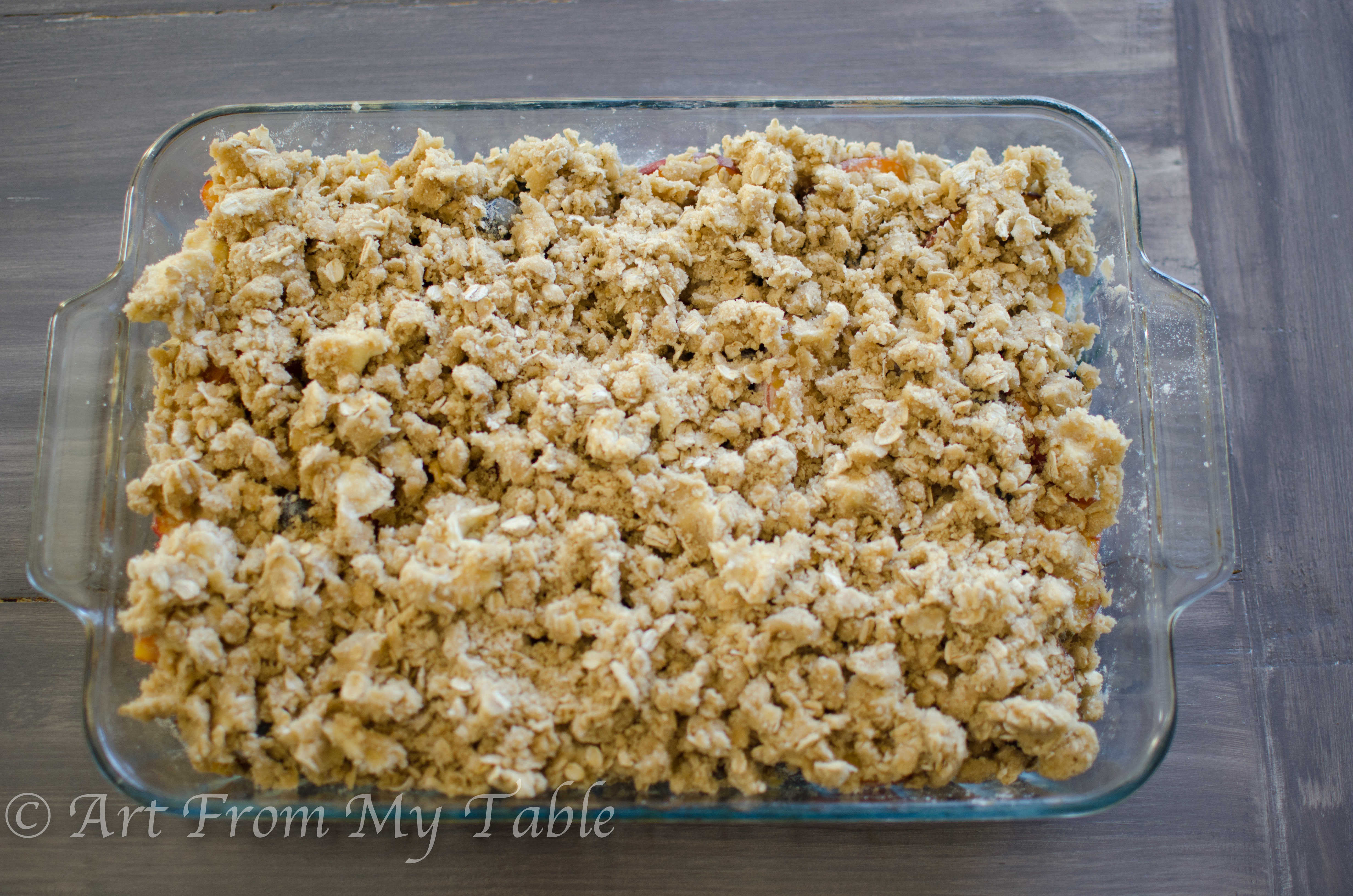 """Blueberries and peaches with """"crisp"""" topping ingredients over top, ready for the oven."""