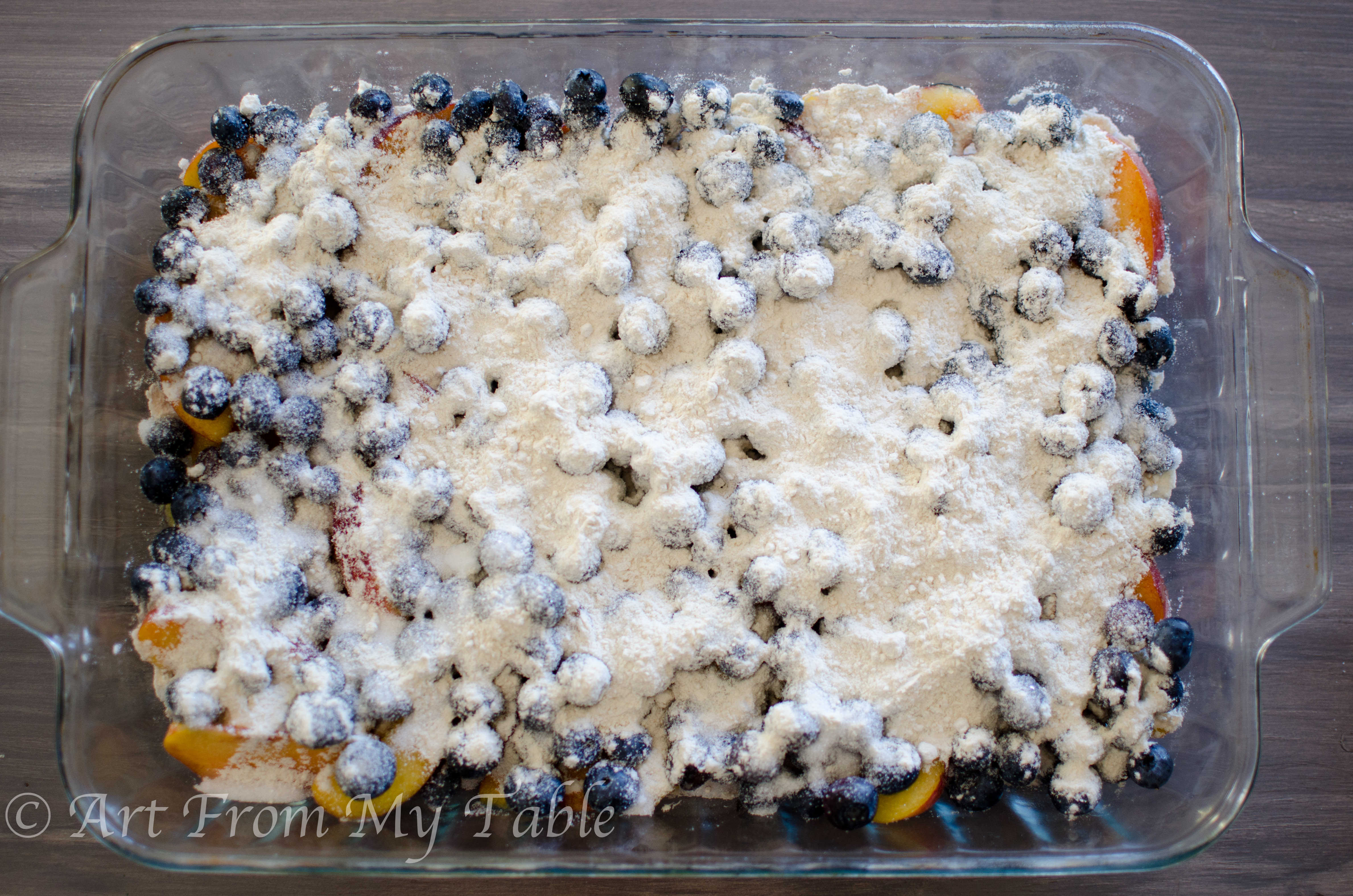 Fresh peaches and blueberries with sugar and flour sprinkled over top.