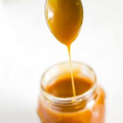 spoon dripping with homemade caramel sauce into a jam jar.
