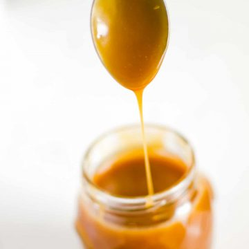 spoon dripping with homemade caramel sauce into a jam jar.