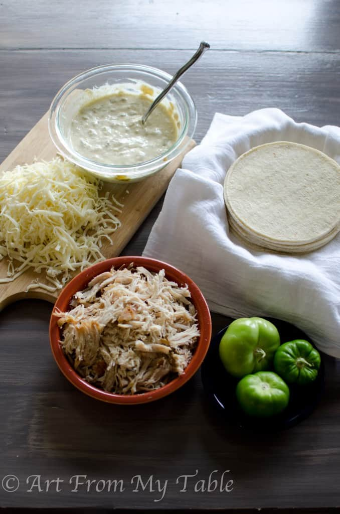 prepped ingredients for carnitas casserole verder, shredded cheese, verde sauce, shredded pork, corn tortillas