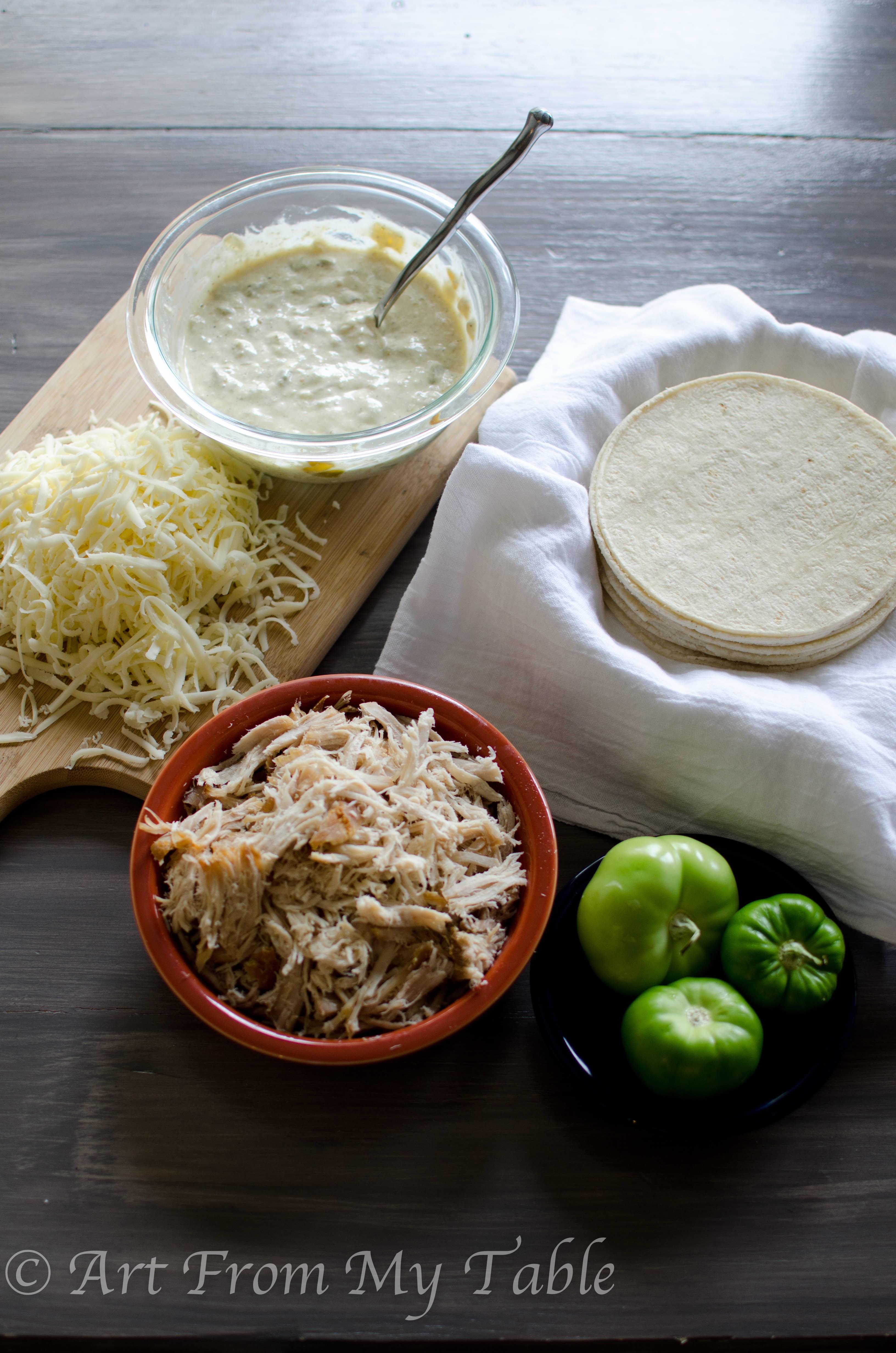 prepped ingredients for carnitas casserole verder, shredded cheese, verde sauce, shredded pork, corn tortillas