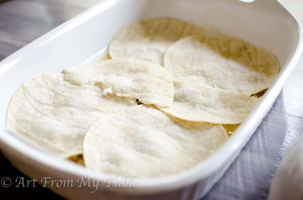 white casserole dish with a layer of soft tortillas