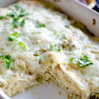 baked carnitas casserole verde in a white dish with one piece removed