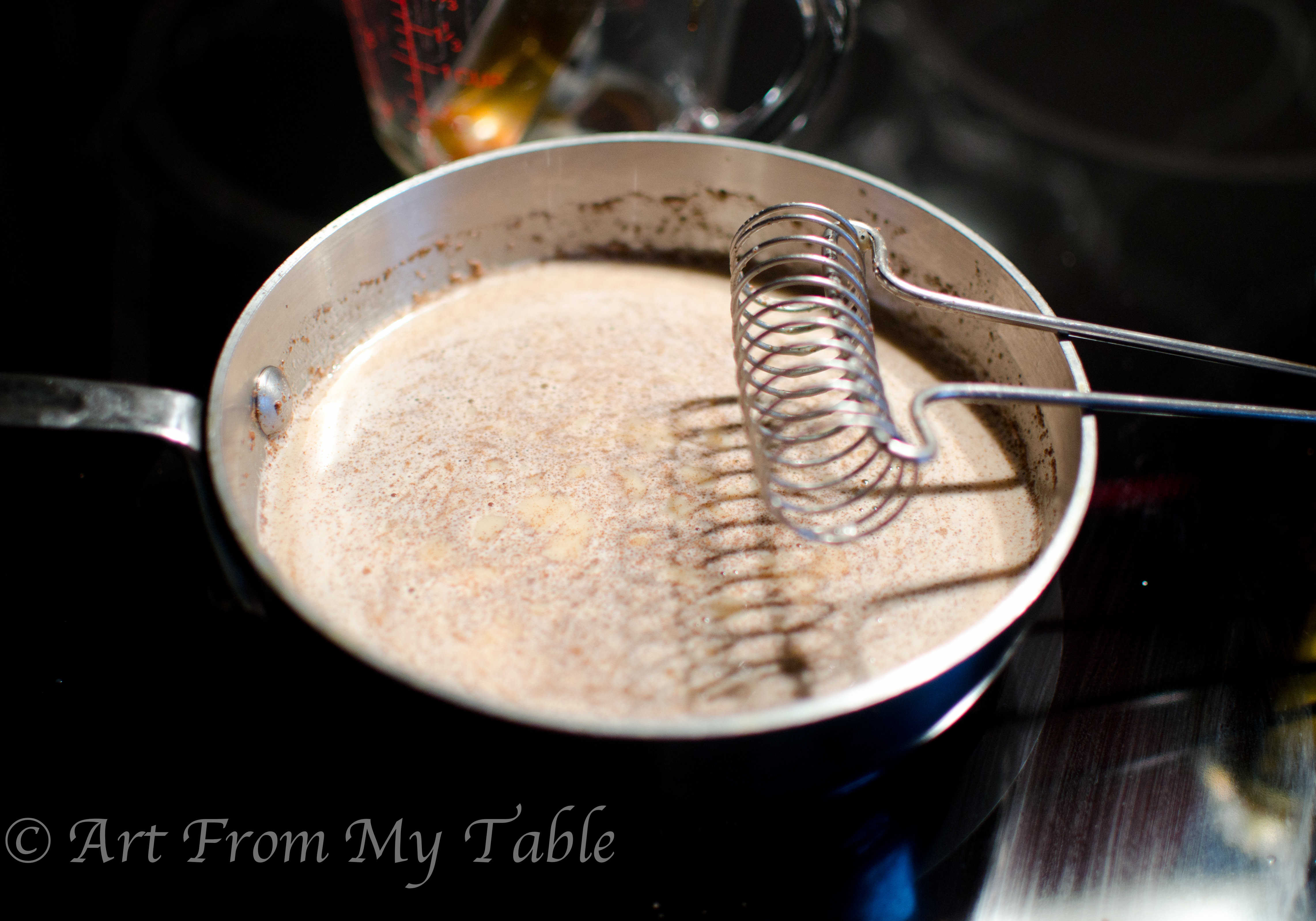 Warm milk in a pan with spices whisked in.