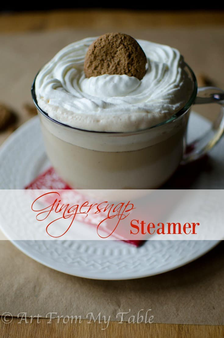 Gingersnap steamer in a glass mug topped with homemade whipped cream and a gingersnap cookie.