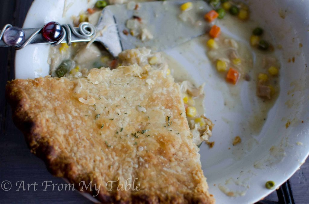 pie plate with one slice of turkey pot pie left in it, with a pretty spatula on the side