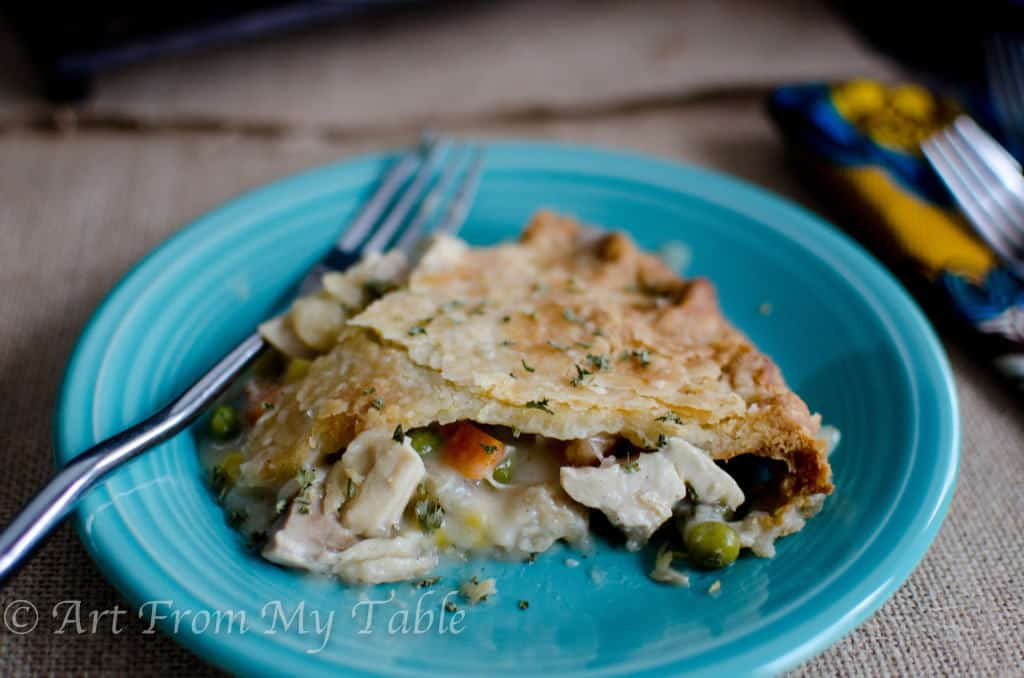 slice of turkey pot pie on a blue plate with a fork next to it. flakey golden crust with some filling oozing out.