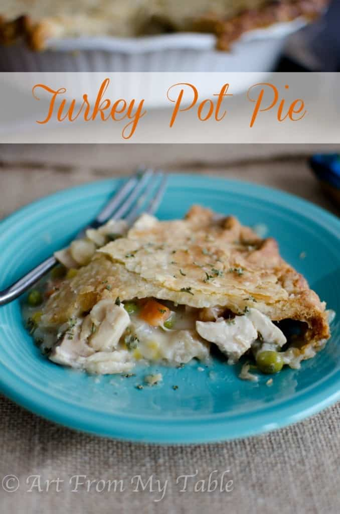 slice of turkey pot pie on a plate, creamy sauce oozing out
