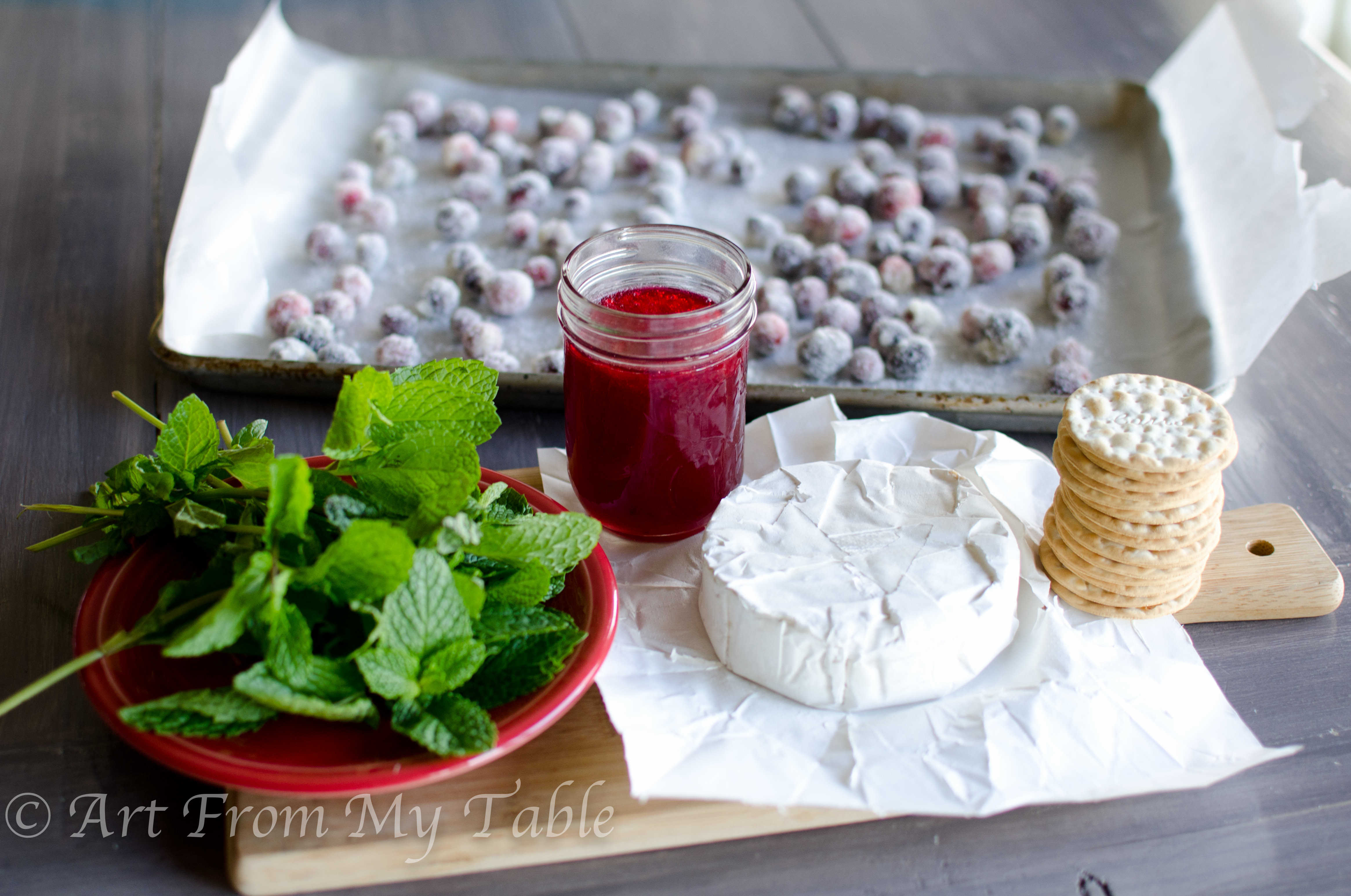Ingredients for cranberry brie bites: crackers, brie, cranberry sauce, sugared cranberries, and fresh mint leaves.