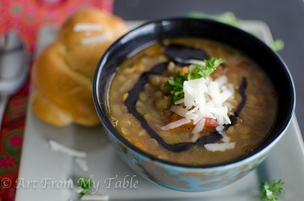 bowl of steaming lentil soup garnished with balsamic vinegar and shredded parmesan cheese