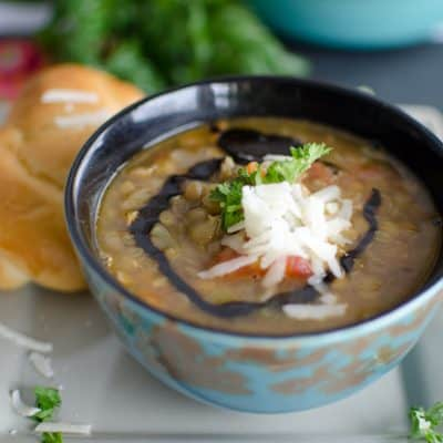 steaming bowl of lentil soup topped with a swirl of balsamic vinegar, shreds of parmesan cheese and parsley with a garlic knot on the side.