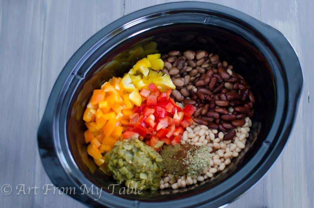 crockpot full of chopped peppers, onions, beans, chiles and seasonings for slow cooker turkey chili