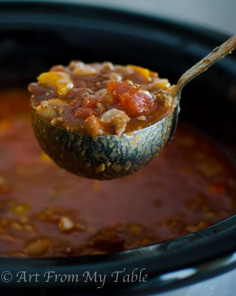 ladle full of turkey chili hovering over a slow cooker full of it