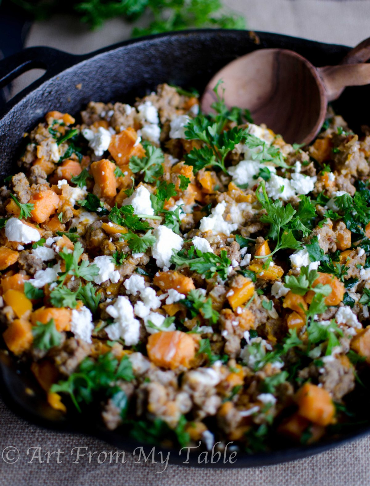 Turkey skillet dinner is a cast iron skillet full of ground turkey, kale, sweet potato chunks and goat cheese garnished with fresh parsley