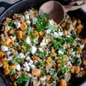 turkey skillet dinner: wooden spoon, ground turkey, diced sweet potato, kale and goat cheese in a cast iron skillet