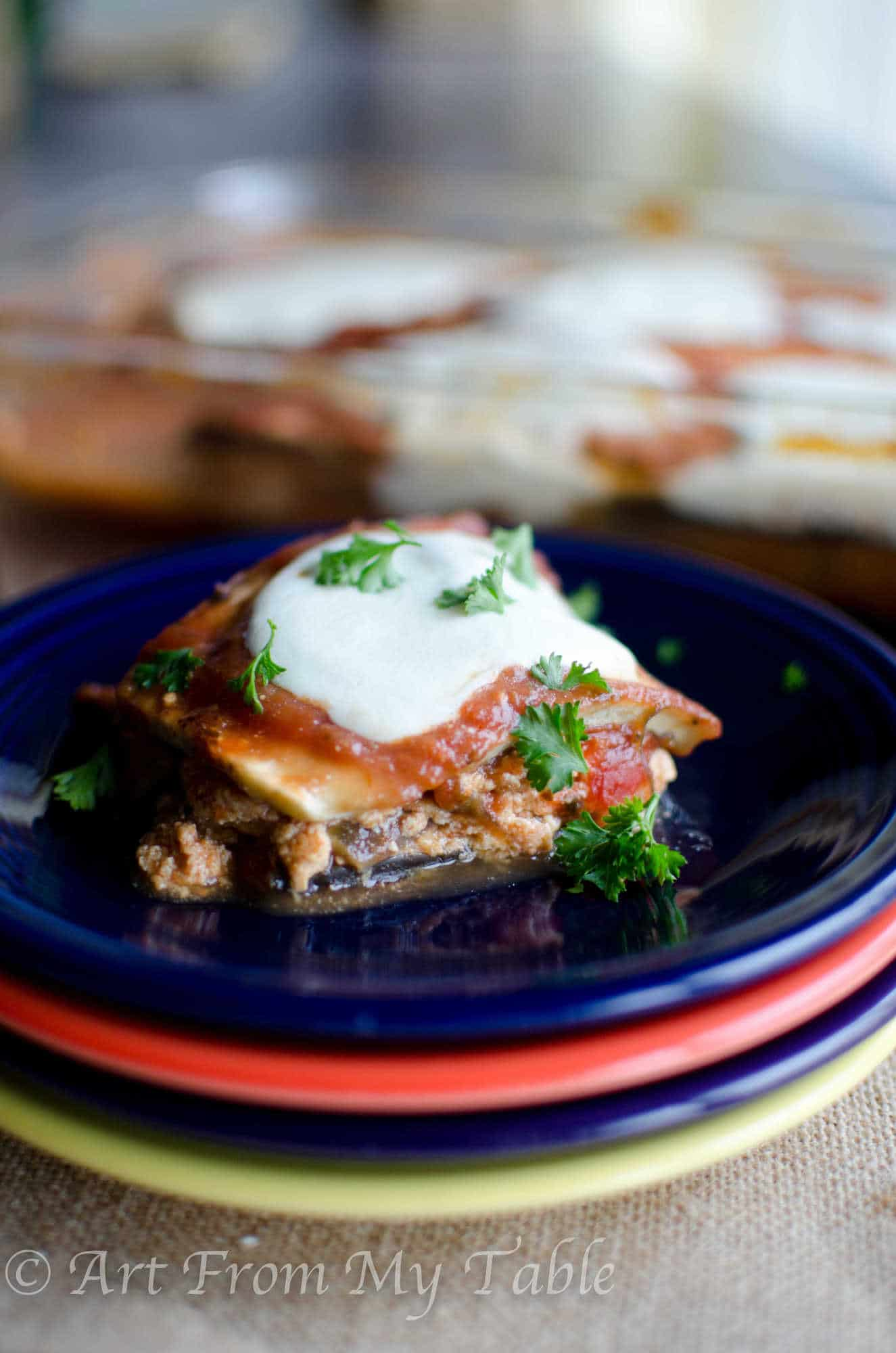 a piece of eggplant lasagna placed on a plate topped with fresh mozzarella cheese and parsley. Casserole dish blurred in the background