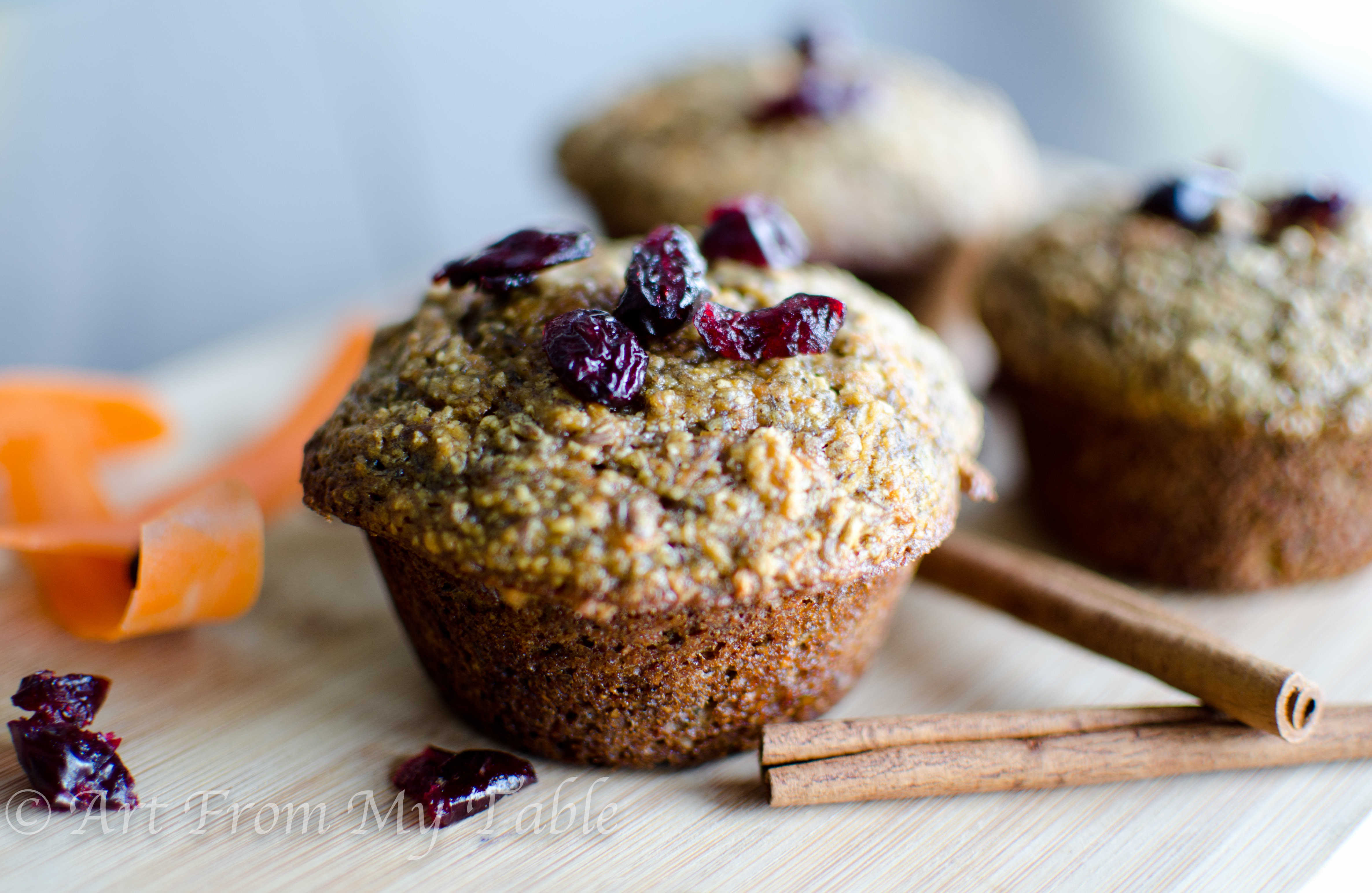 Bran flax muffins with a couple of cinnamon sticks and craisins next to it.