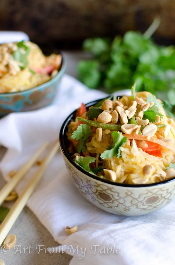 2 bowls piled high with Thai style spaghetti squash 'noodles' and topped with peanuts and cilantro
