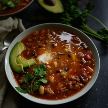 steaming bowl of healthy turkey chili garnished with slices of avocado, cilantro and plain yogurt