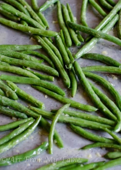Garlic roasted green beans scattered on a baking sheet.