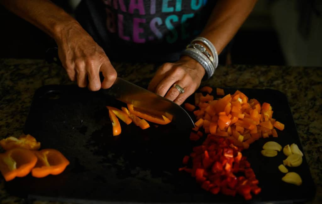 woman slicing orange bell peppers