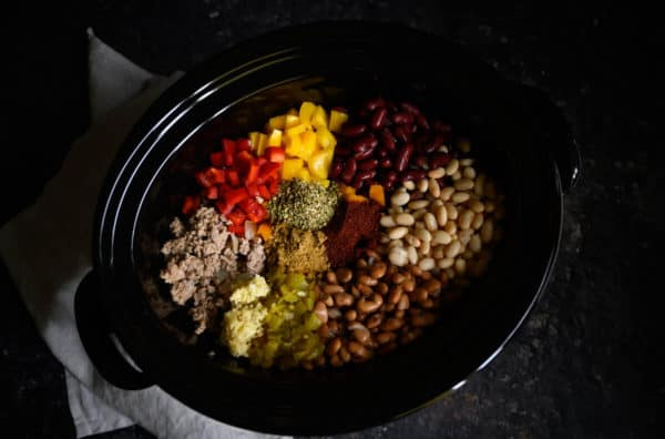 beans, bell peppers, ground turkey, garlic, chili peppers, cumin, oregano, and chili powder in a crockpot.