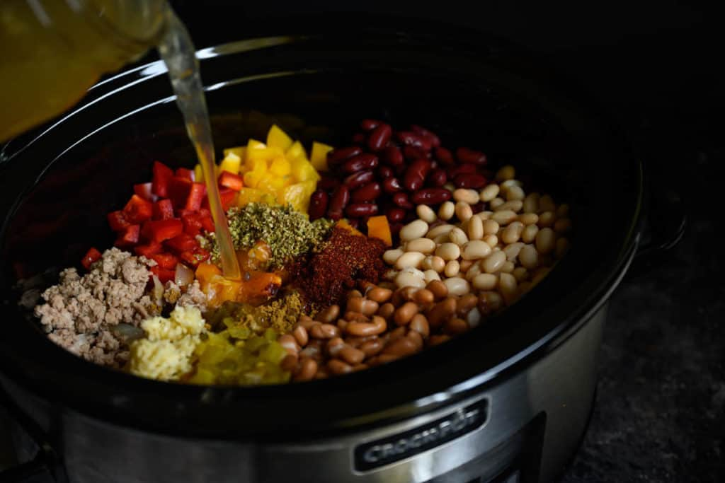 ground turkey, beans, peppers, and spices in a crockpot chicken broth being poured in.