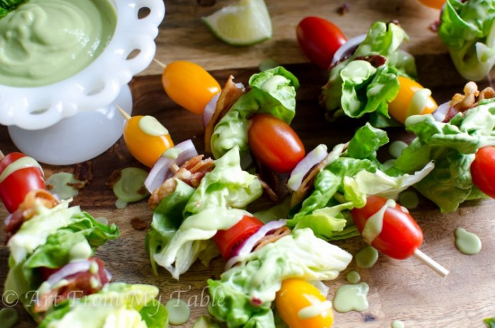 bacon, lettuce, tomato and onion threaded on a skewer for a salad appetizer.