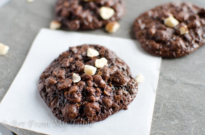 3 chocolate cookies with chopped hazelnuts on top.