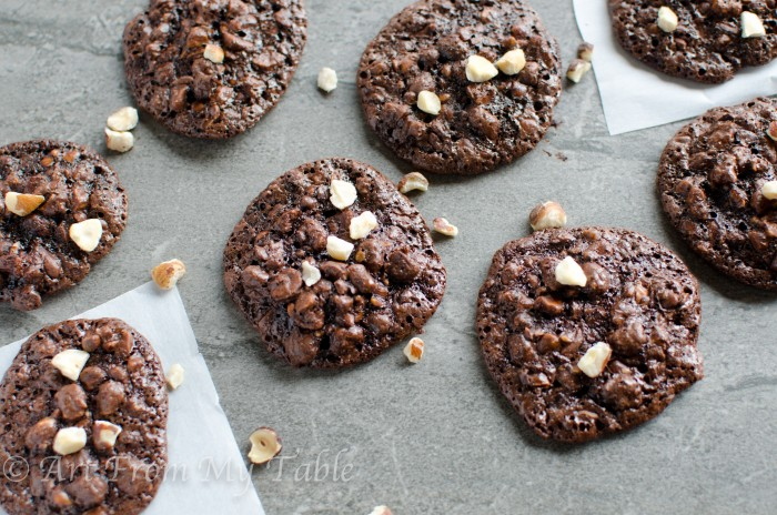 chocolate hazelnut drop cookies on a counter sprinkled with chopped hazelnuts.