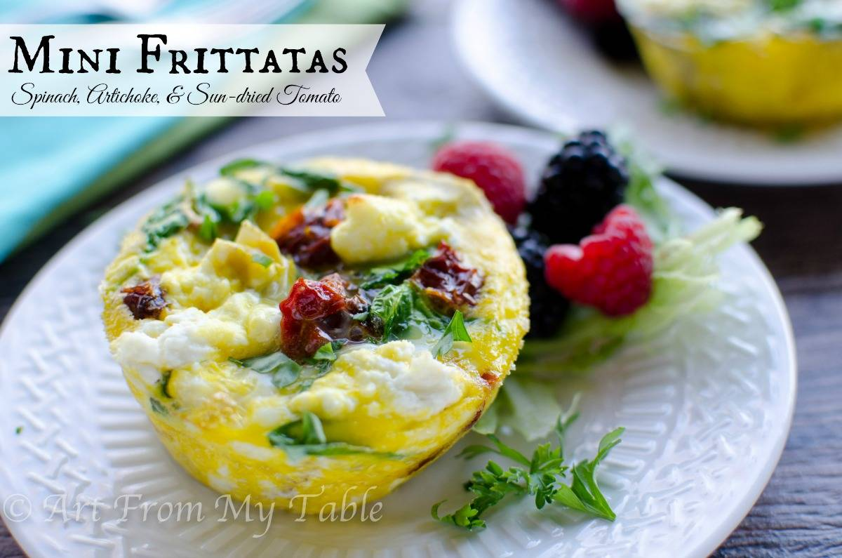 Spinach, artichoke, and sun dried tomato mini frittata on a plate with fresh fruit.