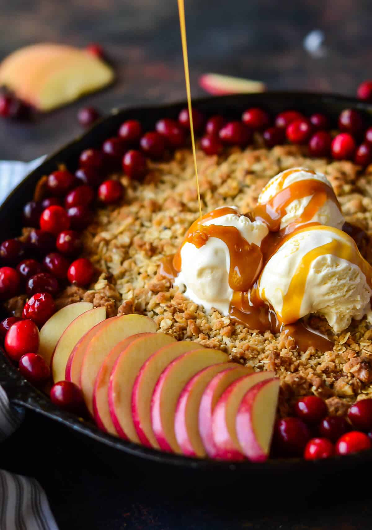caramel sauce being drizzled over maple apple crisp topped with fresh cranberries, fresh apple slices and vanilla ice cream