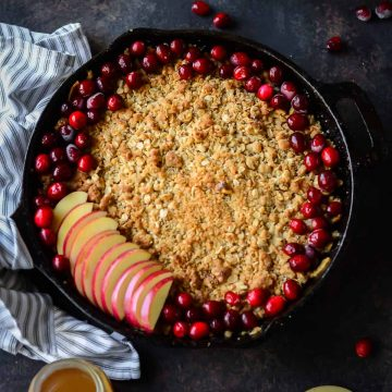 healthy apple crisp baked in a cast iron skillet topped with fresh cranberries and fresh apples