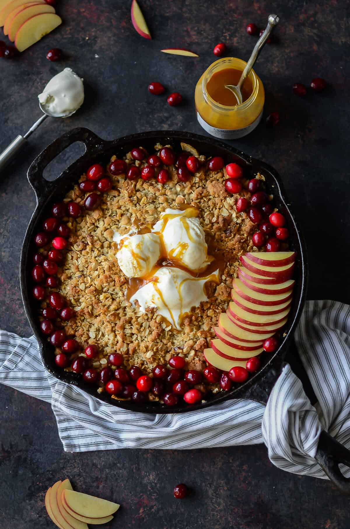 cast iron skillet filled with maple apple crisp and topped with fresh cranberries, apple slices and vanilla ice cream drizzled with caramel sauce