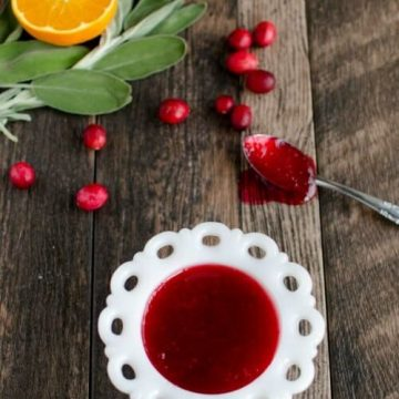 homemade cranberry sauce in a white dish with a spoon full of sauce