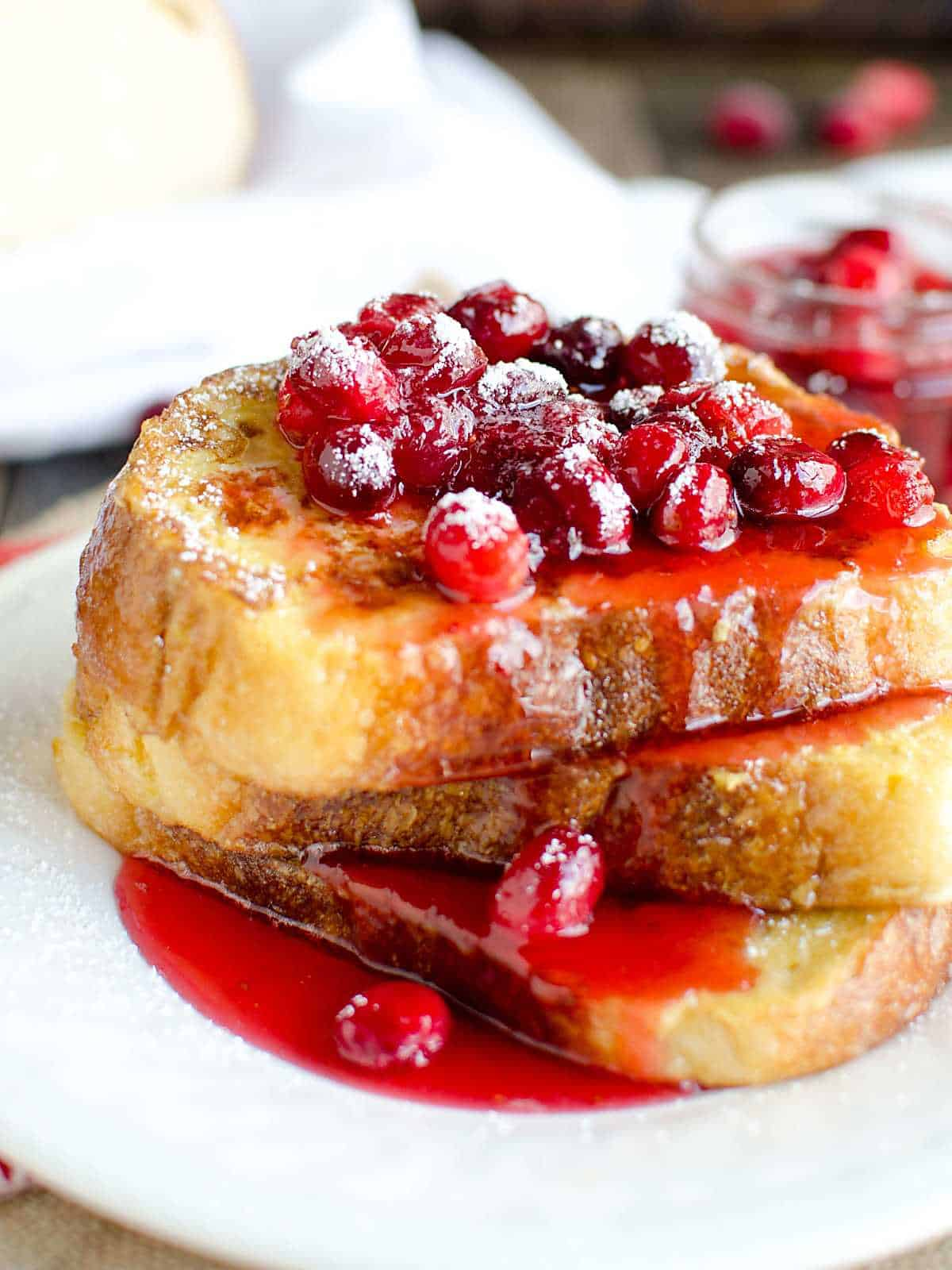 eggnog french toast stacked on a white plate topped with cranberry syrup and powdered sugar.