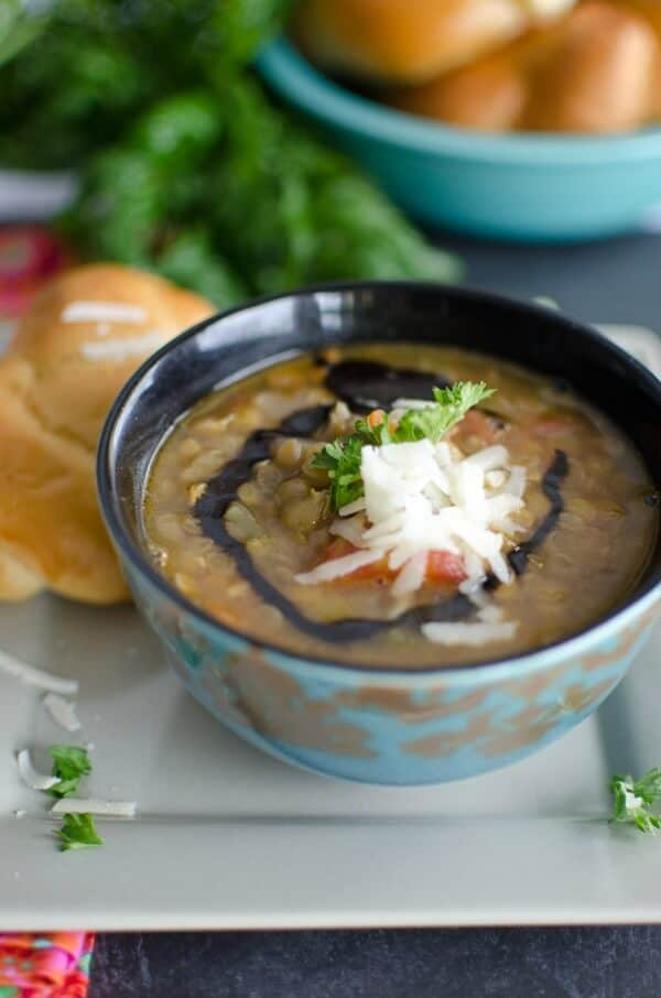Steaming bowl of lentil soup topped with a swirl of balsamic vinegar, shreds of parmesan cheese and parsley